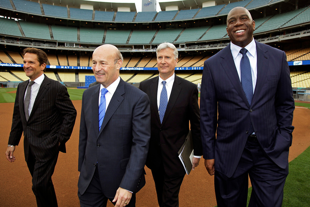 . From left, new Los Angeles Dodgers owners and Guggenheim Baseball Management partners Peter Guber, Stan Kasten, Mark Walter and Magic Johnson walk into Dodger Stadium in Los Angeles, Wednesday, May 2, 2012. The franchise\'s prestige and fan support declined during the stormy ownership tenure of Frank McCourt, who sold the Dodgers for $2 billion to the group fronted by Johnson, headed by Walter and run by Kasten. (AP Photo/Damian Dovarganes)