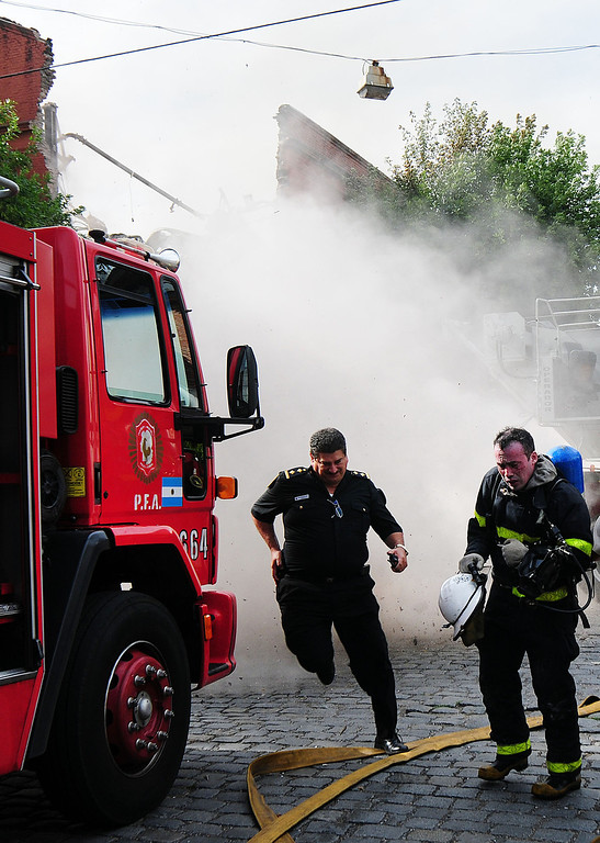 . Picture released by Diario Popular via Noticias Argentinas showing firemen taking cover as they fight a fire at a warehouse in Barracas, in southern Buenos Aires, on February 5, 2014.   AFP PHOTO / NA / DIARIO POPULAR / GUSTAVO FIDANZA   --- DIARIO POPULAR/AFP/Getty Images