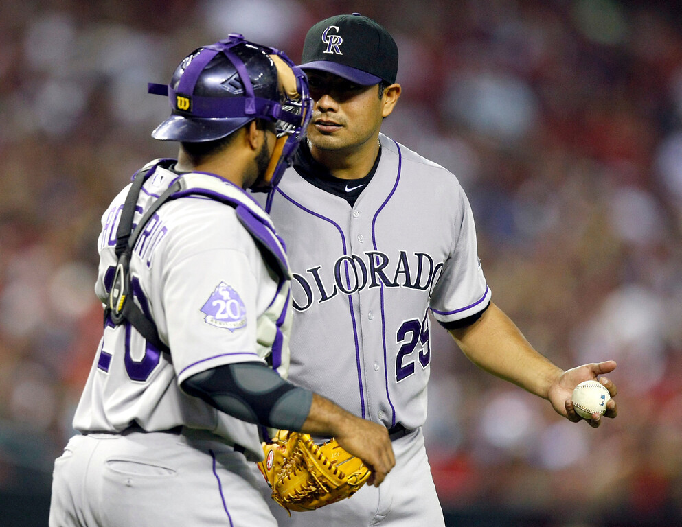 . Colorado Rockies pitcher Jorge De La Rosa, right, talks with Wilin Rosario,left, in the fifth inning during a baseball game against the Arizona Diamondbacks on Friday, July 5, 2013, in Phoenix. (AP Photo/Rick Scuteri)