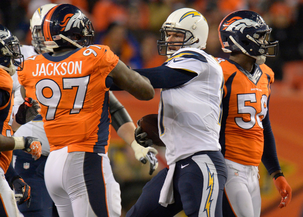 . San Diego Chargers quarterback Philip Rivers (17) pushes Denver Broncos defensive end Malik Jackson (97) after Rivers ran the ball during the first quarter. The Denver Broncos vs. the San Diego Chargers at Sports Authority Field at Mile High in Denver on December 12, 2013. (Photo by John Leyba/The Denver Post)