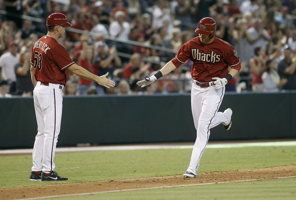 . Nolan Reimold #12 of the Arizona Diamondbacks (R) is congratulated by third base coach Glenn Sherlock #53 after his two-run home run against the Colorado Rockies during the seventh inning of a MLB game at Chase Field on August 31, 2014 in Phoenix, Arizona.  (Photo by Ralph Freso/Getty Images)