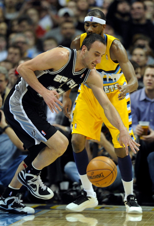 . Spurs guard Manu Ginnobili (20) controlled a rebound in front of Denver gorward Corey Brewer (13) in the first half. The Denver Nuggets hosted the San Antonio Spurs at the Pepsi Center Tuesday night, December 18, 2012. Karl Gehring/The Denver Post