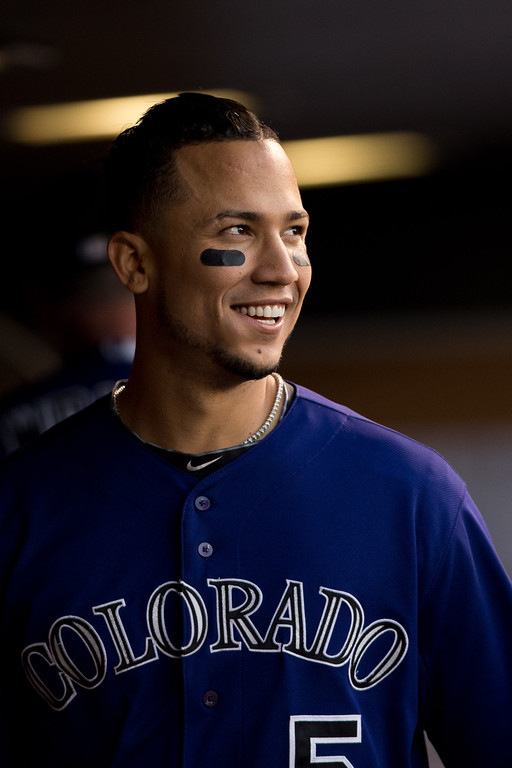 . DENVER, CO - JULY 20:  Carlos Gonzalez #5 of the Colorado Rockies smiles in the dugout after hitting a solo home run against the Chicago Cubs at Coors Field on July 20, 2013 in Denver, Colorado.  (Photo by Justin Edmonds/Getty Images)