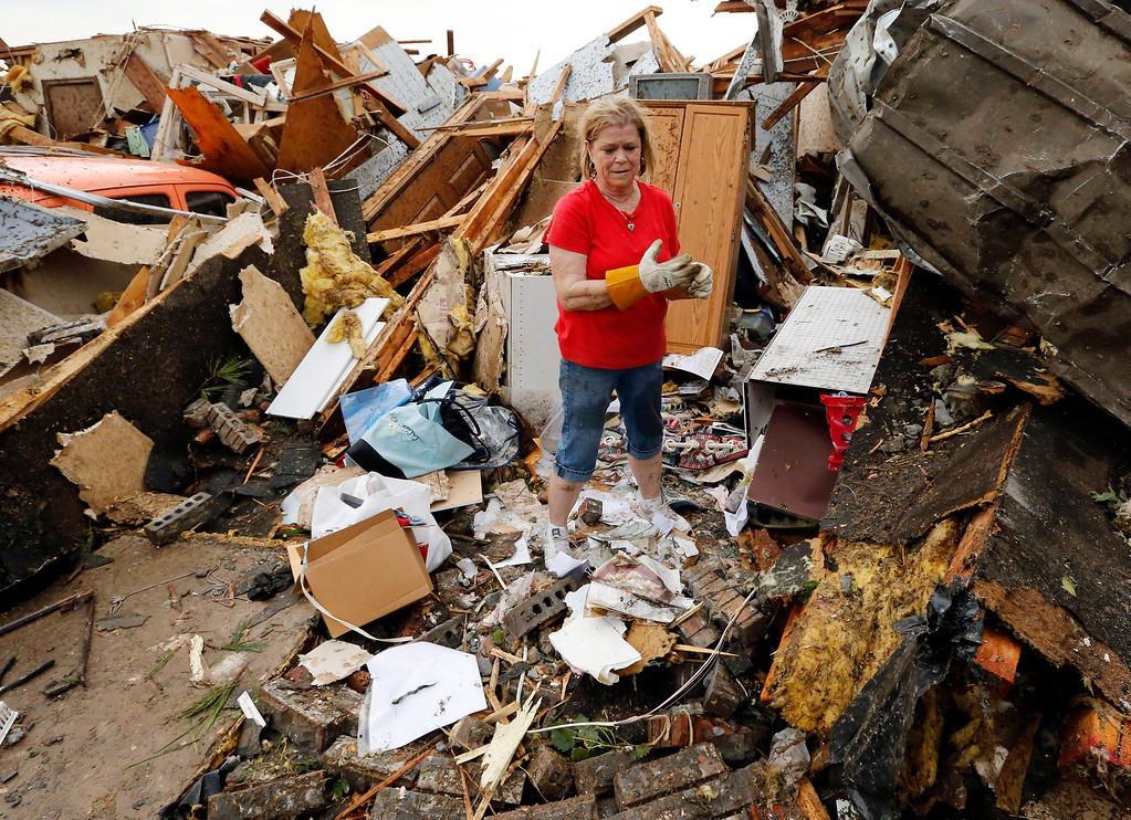 . JoAnn Anderson sorts through the rubble of her home after a tornado on Monday, May 20, 2013  in Moore, Okla. A monstrous tornado roared through the Oklahoma City suburbs, flattening entire neighborhoods with winds up to 200 mph, setting buildings on fire and landing a direct blow on an elementary school. (AP Photo/The Oklahoman, Steve Sisney)