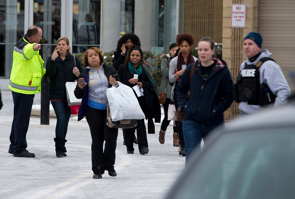 . Police and law enforcement evacuate the Mall of Columbia after a shooting on Saturday, Jan. 25, 2014 in Columbia, Md. Police say three people died in a shooting at the mall in suburban Baltimore, including the presumed gunman. (AP Photo/ Evan Vucci)