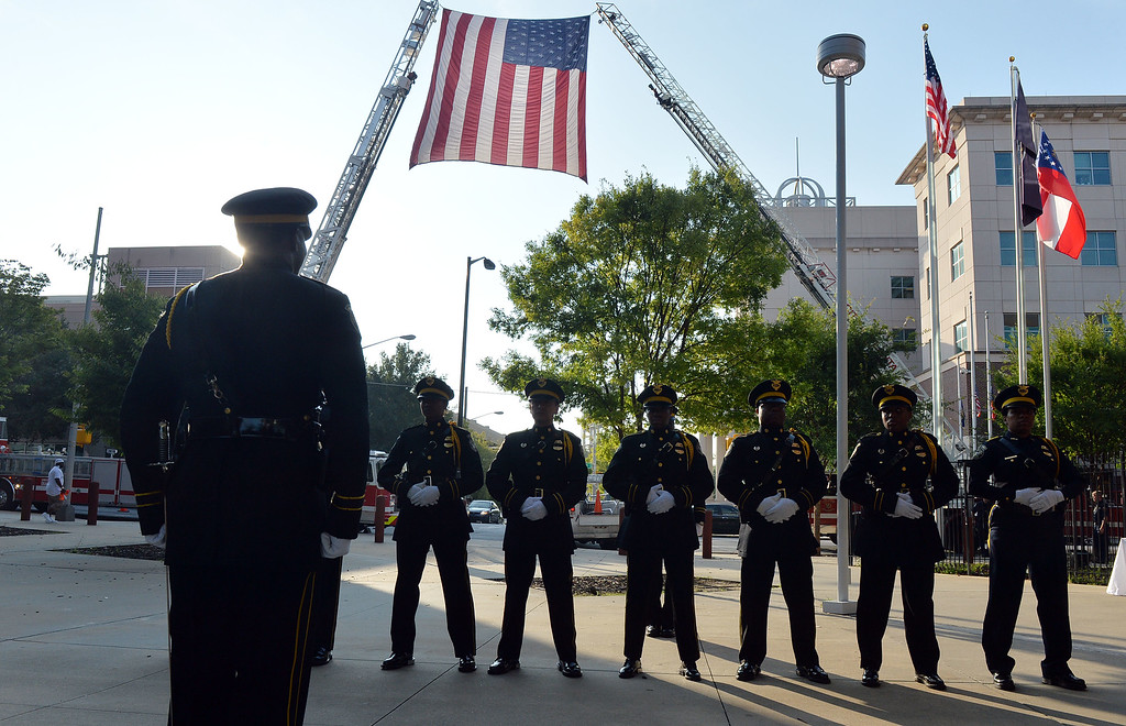 . The Atlanta Police Department Honor Guard stands at rest under a large American flag during a memorial service honoring the 13th anniversary of the Sept. 11, 2001 terrorist attacks at their headquarters in Atlanta, Thursday, Sept. 11, 2014. Atlanta Police Chief George N. Turner and Fire Chief Kelvin J. Cochran as well as Public Saftey committee chairman Atlanta City Councilman C.T. Martin, gave remarks recognizing the many Americans and public safety officials who lost their lives in the attacks.  (AP Photo/Atlanta Journal-Constitution, Kent D. Johnson)