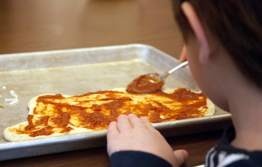 . Kayla Rice/Reformer MJ Iams, 3, of Brattleboro puts tomato sauce on his pizza crust during a cooking class held at the Brattleboro Food Co-Op for the Winter Carnival on Friday afternoon.