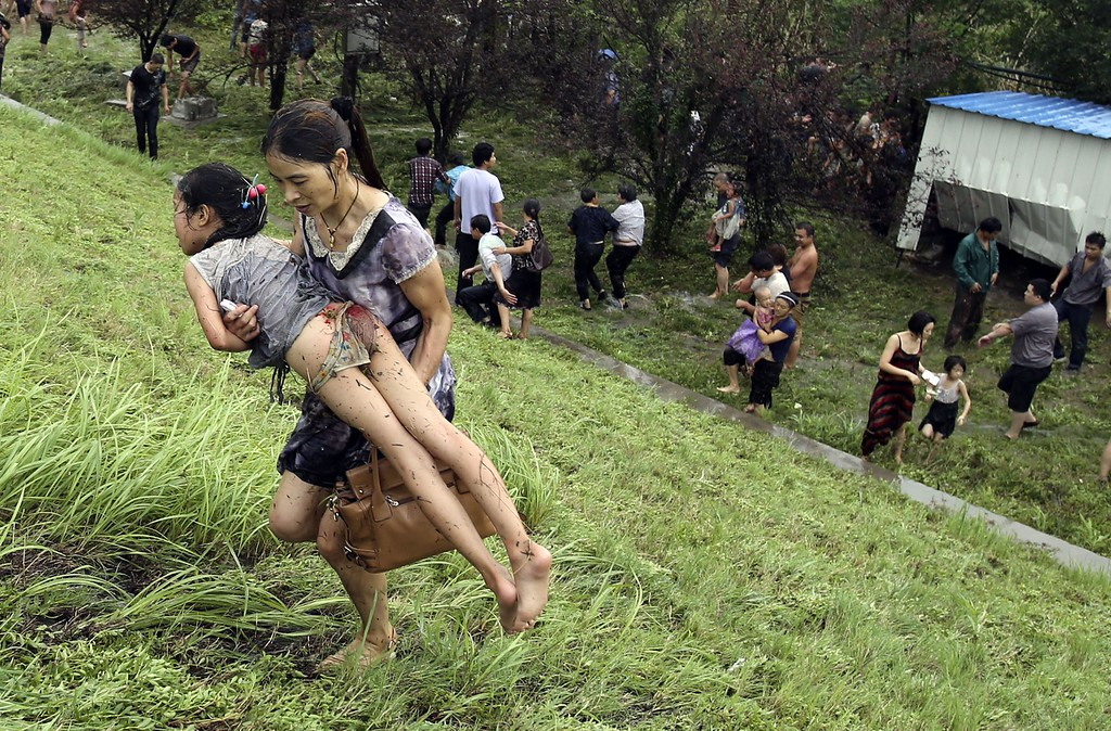 """. This picture taken on August 22, 2013 shows a woman carrying an injuried girl after they were washed down a hill from huge waves from the \""""Haining tide\"""" - a daily occurrence when the river tides hit the banks of the city - after a wave surged higher than usual due to the influence of Typhoon Trami in the region in Haining, in eastern China\'s Zhejiang province.      AFP PHOTOSTR/AFP/Getty Images"""