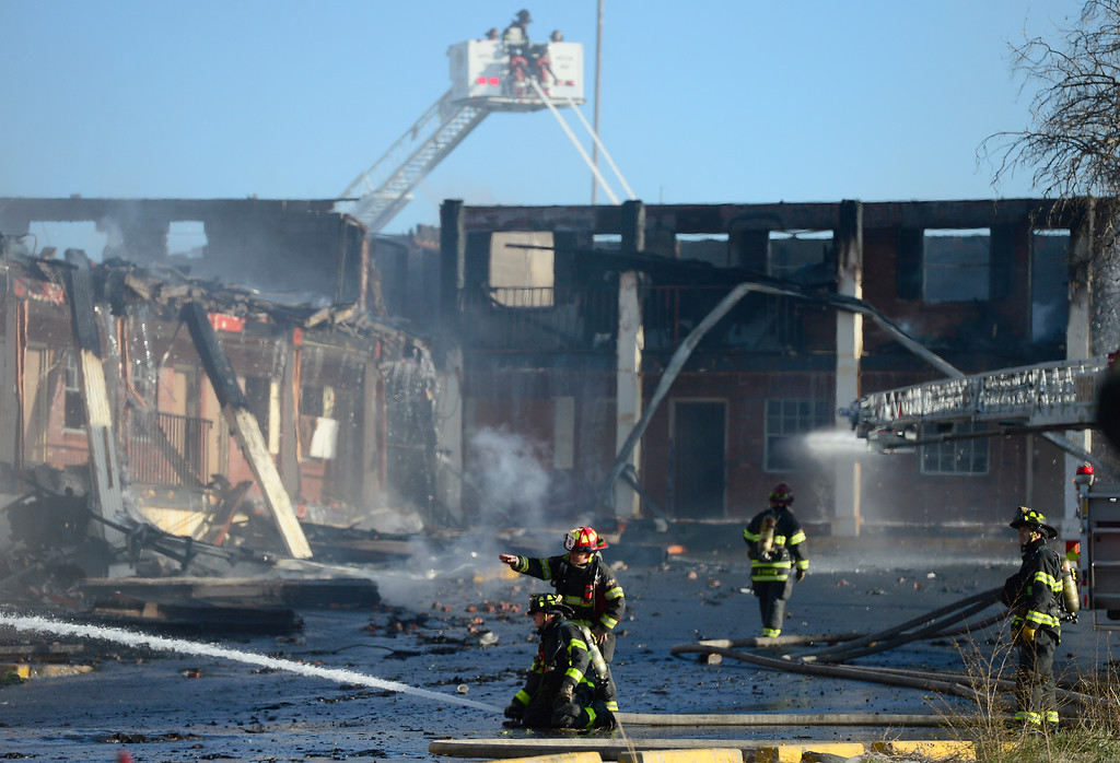 . Firefighters work to extinguish a fire at the former Rockies Inn near I-25 and Evans Avenue on April 1, 2016 in Denver, Colorado. The fire, that started in the late afternoon, destroyed the vacant motel causing a wall to fall onto an adjacent building. No injuries were reported. (Photo by Brent Lewis/The Denver Post)