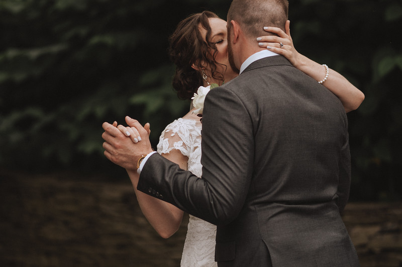 The bride and groom embracing into a kiss.