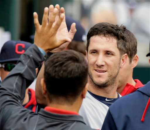 . Cleveland Indians\' Yan Gomes celebrates in the dugout after scoring against the Detroit Tigers during the sixth inning of a baseball game Sunday, Sept. 14, 2014, in Detroit. (AP Photo/Duane Burleson)