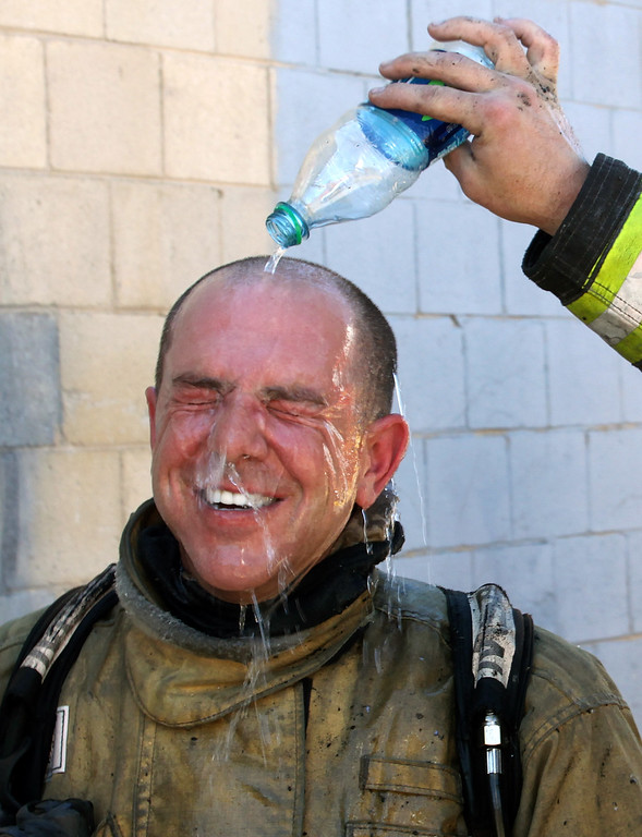 . A Salt lake City fireman pours a cold bottle of water over the head of fireman Cary Turner after battling a house fire Thursday, June 26, 2013, in Salt lake City. Temperatures in Utah are approaching record highs and a heat advisory will be in effect for central and western parts of southern Utah through the weekend. The National Weather Service has issued a hazardous weather outlook for the western two-thirds of the state. (AP Photo/Rick Bowmer)
