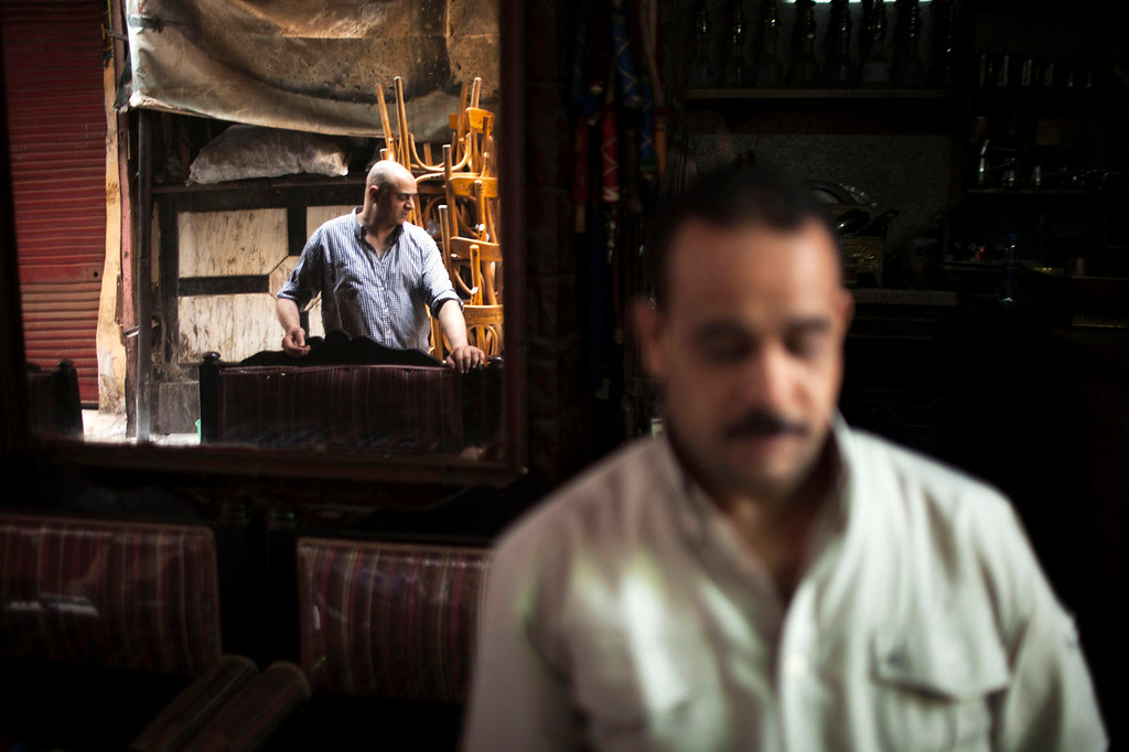 . An Egyptian man is seen reflected on a mirror of his coffee shop in the Khan El-Khalili market, normally a popular tourist destination, in Cairo, Egypt, Wednesday, Aug. 21, 2013. Riots and killings that erupted across the country after the crackdown against followers of ousted President Mohammed Morsi have delivered a severe blow to Egypt\'s tourism industry, which until recently accounted for more than 11 percent of the country\'s gross domestic product and nearly 20 percent of its foreign currency revenues. (AP Photo/Manu Brabo)