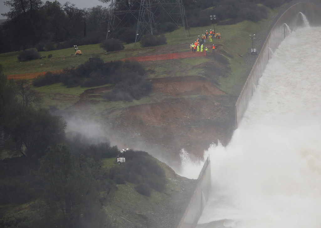 ". Water flows through break in the wall of the Oroville Dam spillway, Thursday, Feb. 9, 2017, in Oroville, Calif. Engineers don\'t know what caused what state Department of Water Resources spokesman Eric See called a ""massive\"" cave-in that is expected to keep growing until it reaches bedrock. (AP Photo/Rich Pedroncelli)"