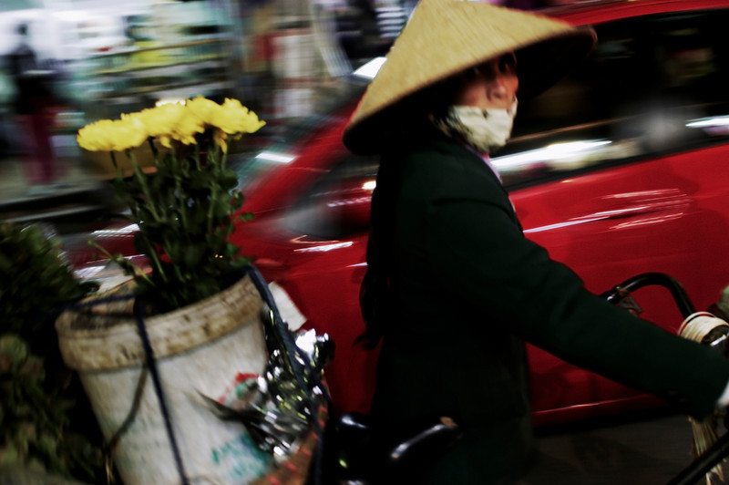Woman selling flowers from her bicycle amidst the chaotic traffic in Hanoi.