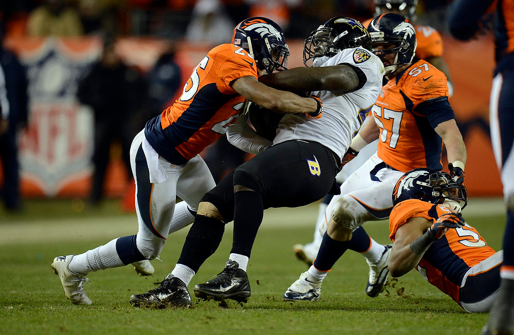 . Denver Broncos cornerback Chris Harris (25) takes down Baltimore Ravens fullback Vonta Leach (44) during the fourth quarter.  The Denver Broncos vs Baltimore Ravens AFC Divisional playoff game at Sports Authority Field Saturday January 12, 2013. (Photo by Joe Amon,/The Denver Post)