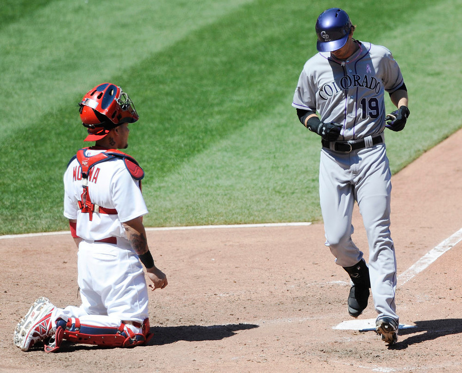 . Colorado Rockies\' Charlie Blackman (19) crosses the plate after his two-run home run as St. Louis Cardinals\' Yadier Molina looks on in the sixth inning in a baseball game on Sunday, May 12, 2013, at Busch Stadium in St. Louis. (AP Photo/Bill Boyce)