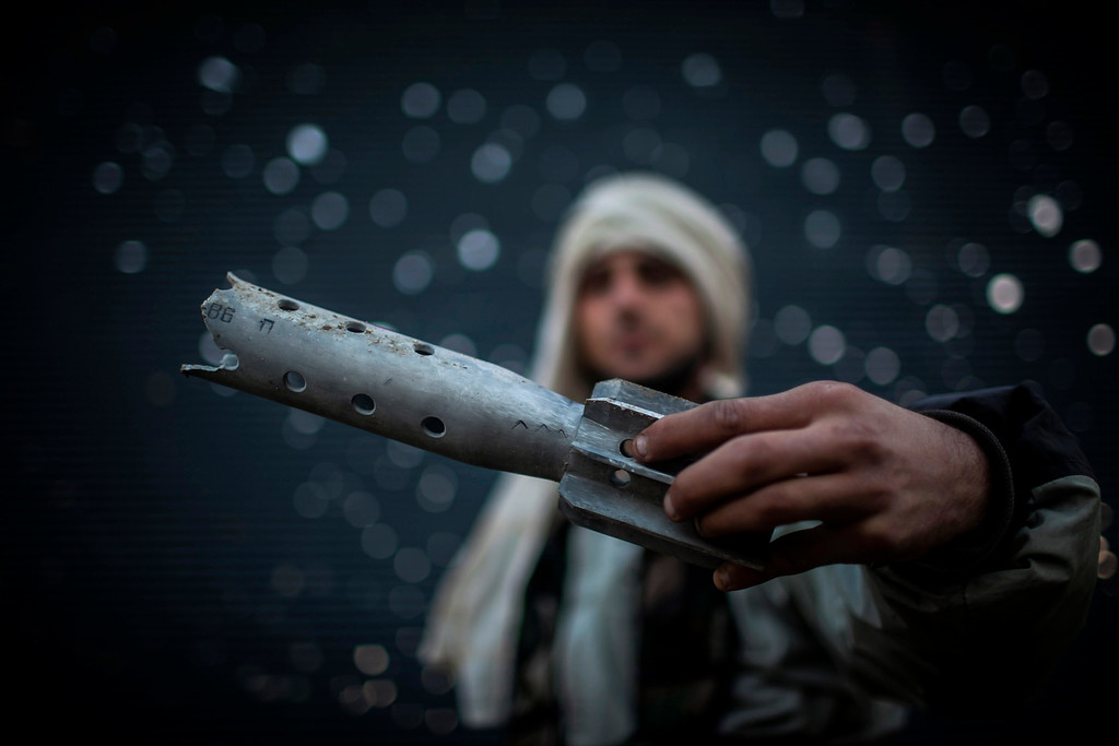 . FILE - A Free Syrian Army fighter displays a damaged ordinance in Aleppo, Syria, Tuesday, Jan. 15, 2013. (AP Photo/Andoni Lubaki, File)