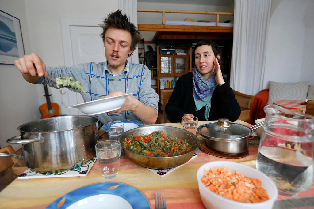 . Raphael Fellmer (L), a supporter of the foodsharing movement has lunch with his partner Nieves Palmer Muntaner, with food cooked from vegetables from waste of an organic supermarket in Berlin, January 24, 2013. Foodsharing is a German internet based platform where individuals, retailers or producers have the possibility of offering surplus food to consumers for free. Picture taken January 24.   REUTERS/Fabrizio Bensch