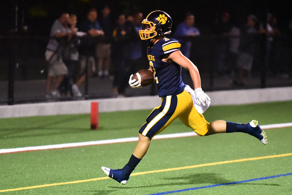 . Littleton quarterback Will Scott carries the ball into the endzone at the start of the second half during Friday night\'s game at home against Hudson.  Sun/Jeff Porter