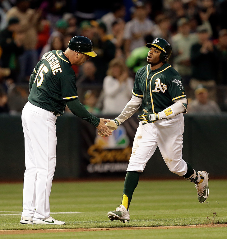 . Oakland Athletics\' Khris Davis, right, is congratulated by third base coach Steve Scarsone after hitting a home run off Cleveland Indians\' Carlos Carrasco during the fifth inning of a baseball game Friday, July 14, 2017, in Oakland, Calif. (AP Photo/Ben Margot)