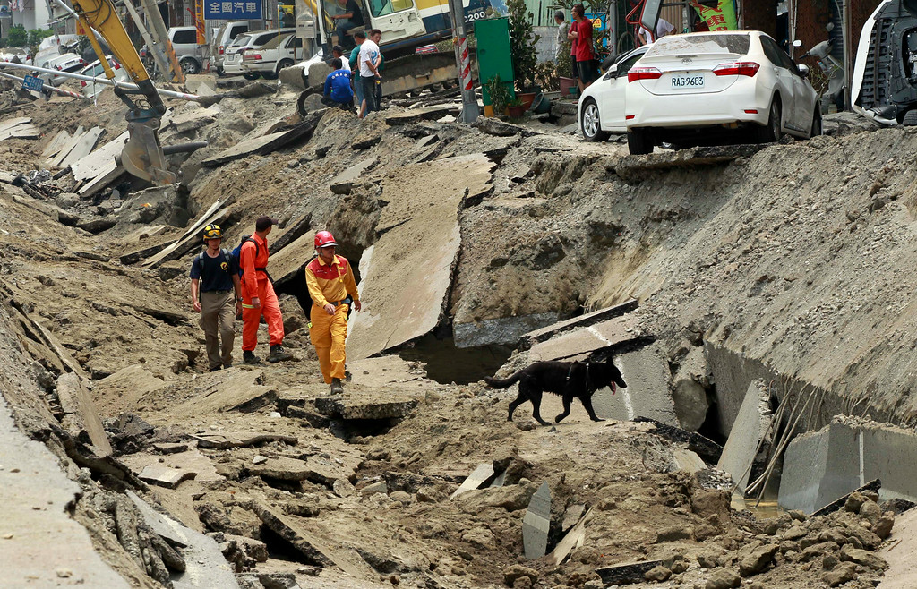 . An emergency rescue team uses a sniffer dog to look for missing persons after massive gas explosions in Kaohsiung, Taiwan, Friday, Aug. 1, 2014. A series of explosions about midnight Thursday and early Friday ripped through Taiwan\'s second-largest city, killing scores of people, Taiwan\'s National Fire Agency said Friday. (AP Photo/Wally Santana)