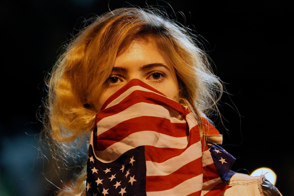 . A woman wears a U.S. flag in front of her face during a rally near the Los Angeles Police Department headquarters in downtown Los Angeles on Tuesday, Nov. 25, 2014. People protesting the Ferguson Mo., grand jury decision took to the streets in cities across the U.S. for the second day. (AP Photo/Nick Ut)