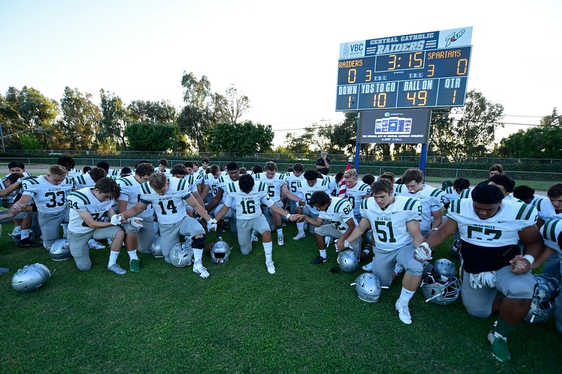 De La Salle players gather to pray before the start of their game at Central Catholic High School in Modesto, Calif. on Friday, Aug. 30, 2019. (Jose Carlos Fajardo/Bay Area News Group)