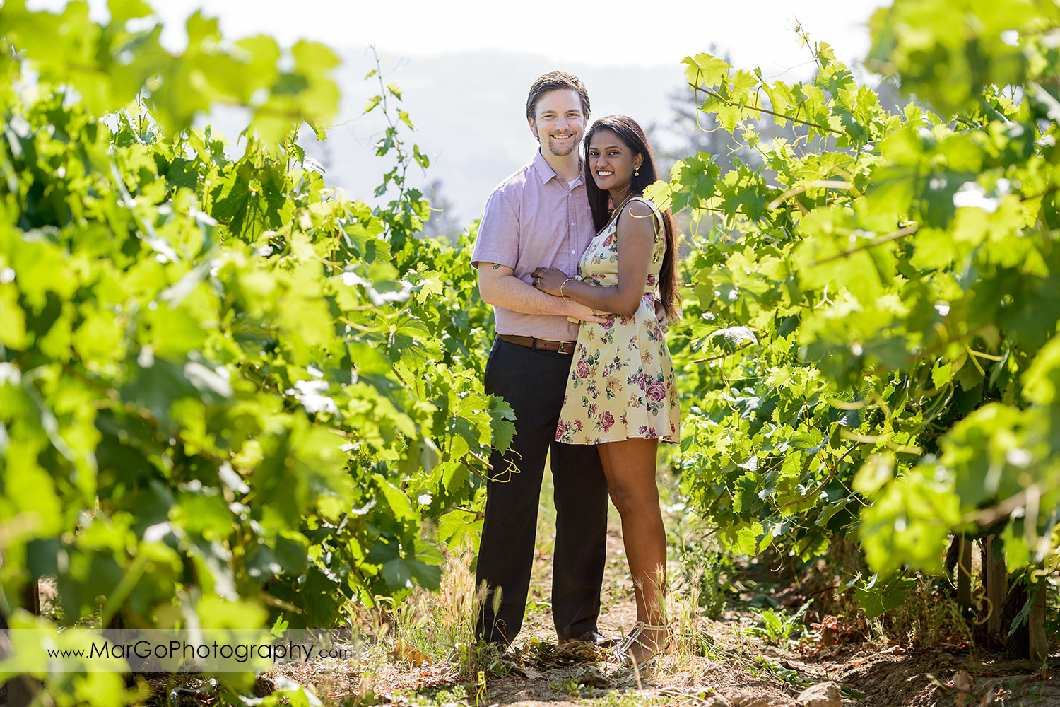 full body portrait of man in pink shirt and Indian woman in flower dress looking into camera in the vineyard during engagement session at Castello di Amorosa in Calistoga