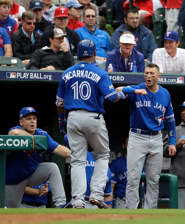 . Toronto Blue Jays manager John Gibbons, left, and Troy Tulowitzki, right, celebrate with Edwin Encarnacion (10) after his solo home run off of Texas Rangers\' Yu Darvish in the fifth inning of Game 2 of baseball\'s American League Division Series, Friday, Oct. 7, 2016, in Arlington, Texas. (AP Photo/David J. Phillip)