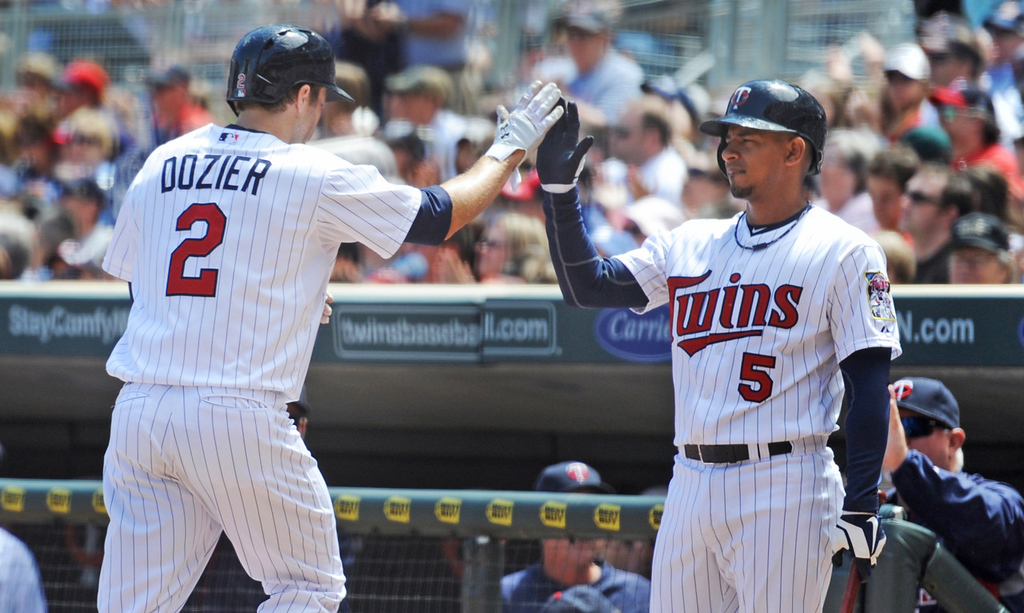 . Minnesota\'s Brian Dozier, left, celebrates with teammate Eduardo Escobar after Dozier scored on an Aaron Hicks\' double during the Twins\' three-run second inning rally against of a baseball game, Sunday, June 2, 2013, in Minneapolis. (AP Photo/Craig Lassig)