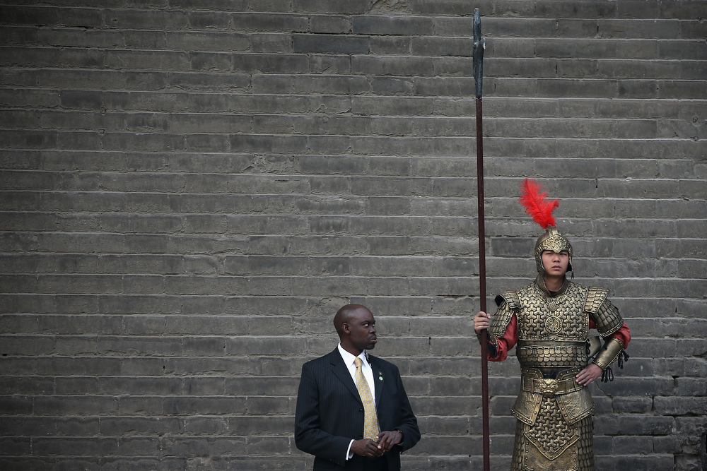 . A security guard of U.S. first lady Michelle Obama stands beside a man wearing a Chinese ancient warrior costume during Obama\'s visit at the City Wall on March 24, 2014 in Xi\'an, China.  Michelle Obama\'s one-week-long visit in China will be focused on educational and cultural exchanges.  (Photo by Feng Li/Getty Images)