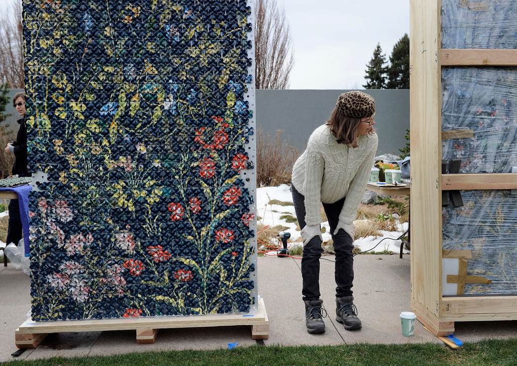. Artist Kim Dickey, watches as volunteers help unwrap her 20 foot ceramic wall covered in ceramic flowers. Artists and volunteers work on a new art installation, Catalyst: Colorado Sculpture at the Denver Botanic Gardens. (Photo By Kathryn Scott Osler/The Denver Post)