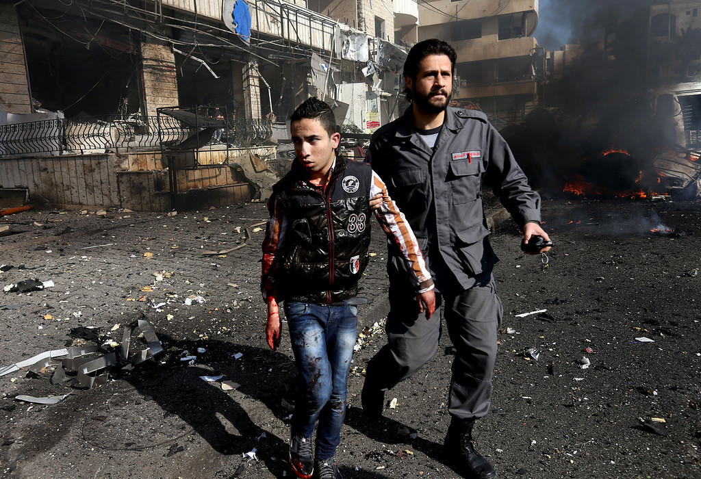 . A Lebanese civil defense worker, right, helps a wounded man at the site of an explosion, near the Kuwaiti Embassy and Iran\'s cultural center, in the suburb of Beir Hassan, Beirut, Lebanon, Wednesday, Feb. 19, 2014.  (AP Photo/Hussein Malla)