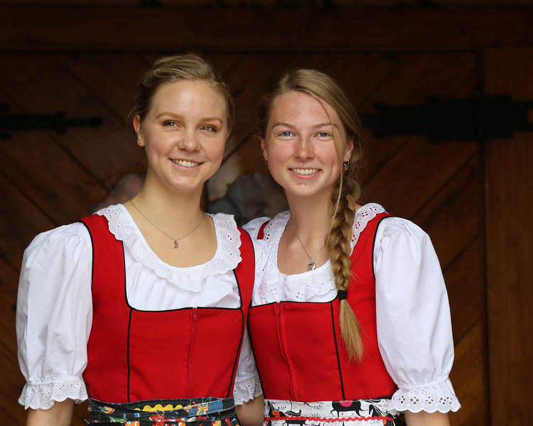 two women dressed in red and white gowns