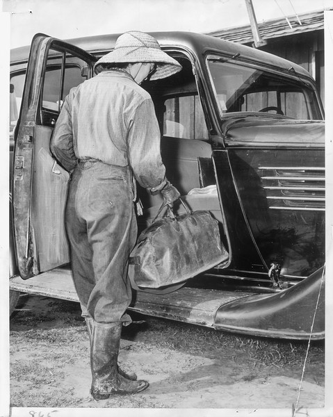 """""""Tei Tsuji, American-born daughter of a Japanese national, here is pictured placing her mother's suitcase in the family car, for her mother must move from their farm in Downey.""""--caption on photograph"""