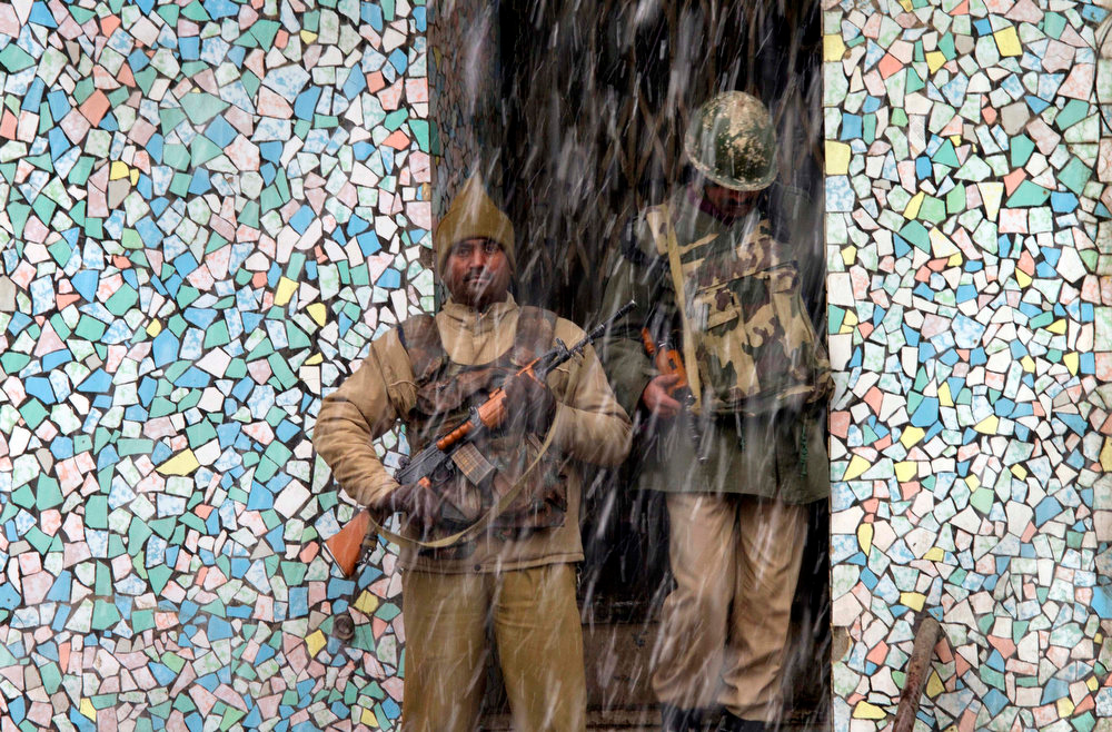 Description of . Indian paramilitary soldiers take shelter from the snow in Srinagar, India, Saturday, Jan. 12, 2013. Traffic on the 300-kilometer (190-mile) long Jammu-Srinagar national highway was suspended due to heavy snowfall, according to news reports. (AP Photo/ Dar Yasin)