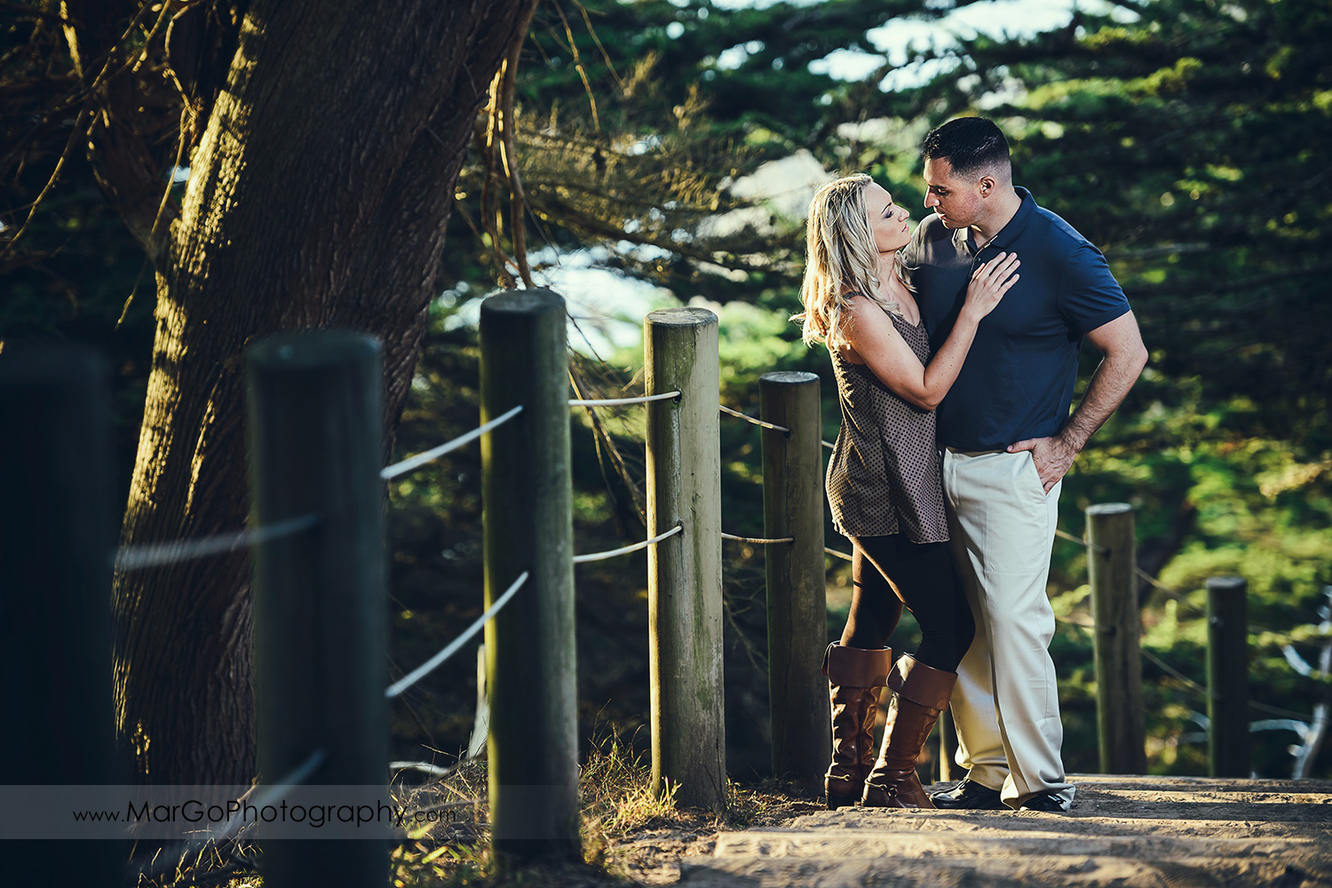 man in navy blue shirt and woman in brown tunic on the wooden stairs looking at each other during engagement session at San Francisco Lands End