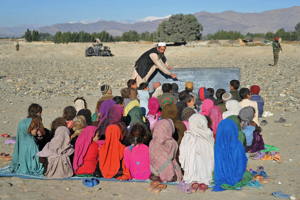 . An Afghan teacher holds an outdoor class in the outskirts of Mihtarlam on December 19, 2012.  Decades of war and conflict in Afghanistan have destroyed hundreds of schools and colleges and many of those who are well-educated have fled to other countries, causing a severe brain drain in the country. Noorullah Shirzada/AFP/Getty Images