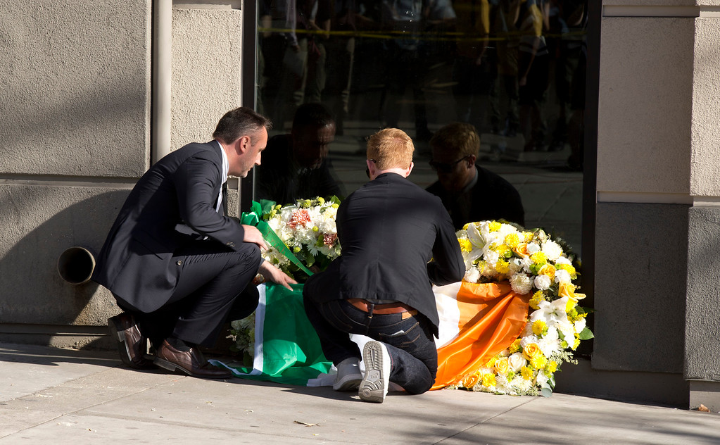 . Philip Grant, Irish Consul General to the Western United States, left, and Neil Sands, once a J-1 visa recipient, lay an Irish flag at the scene where a balcony collapsed, sending 13 people plunging to the street below, Tuesday, June 16, 2015, in Berkeley, Calif. Six people were killed, and seven more were transported to area hospitals. (D. Ross Cameron/Bay Area News Group)