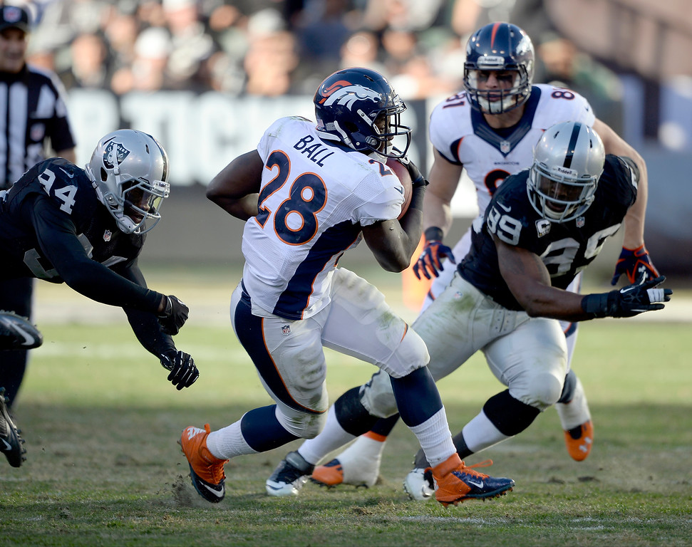 . Denver Broncos running back Montee Ball (28) picks up a few yards as Oakland Raiders defensive end Lamarr Houston (99) chases him down during the third quarter at O.co Coliseum. (Photo by John Leyba/The Denver Post)