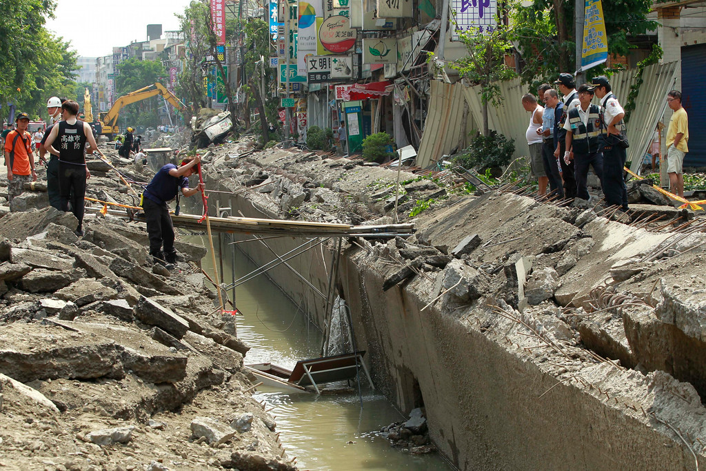 . Rescue workers survey the damage from a massive gas explosion in Kaohsiung, Taiwan, Friday, Aug. 1, 2014. Scores of people were killed and more than 200 others injured when several underground gas explosions ripped through Taiwan\'s second-largest city overnight, hurling concrete through the air and blasting long trenches in the streets, authorities said Friday. (AP Photo/Wally Santana)