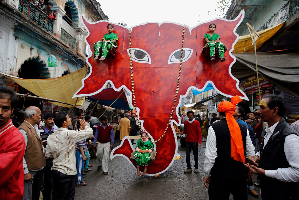 . Young Indian children sit on a huge cut out portrait of elephant\'s head as they participate in a ìShivratriî procession in Allahabad, India, Thursday, Feb. 27, 2014.  (AP Photo/Rajesh Kumar Singh)