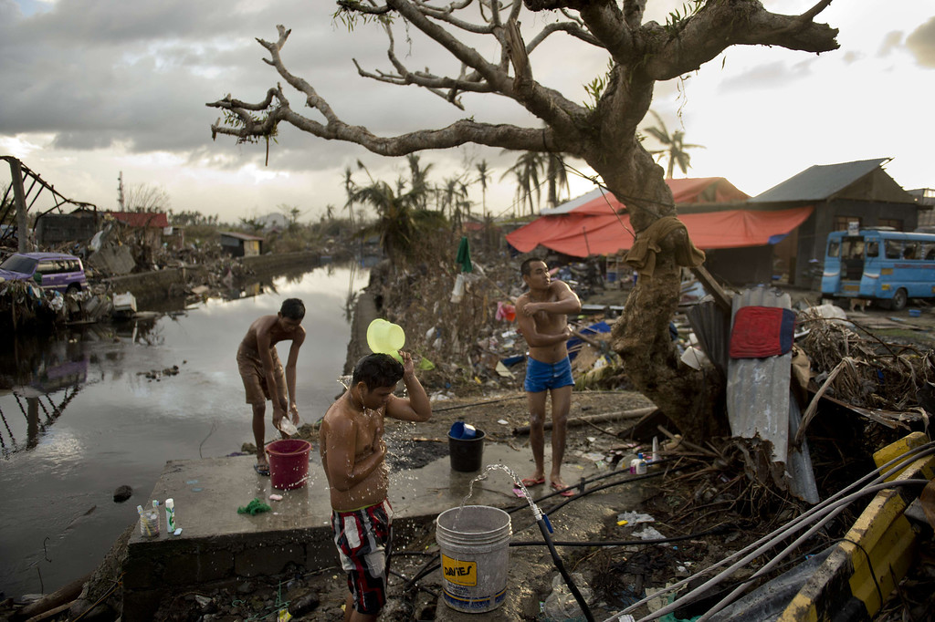 . People wash themselves using water from an open pipe among the rubble of destroyed homes in Tacloban on November 21, 2013.    AFP PHOTO / ODD ANDERSEN/AFP/Getty Images