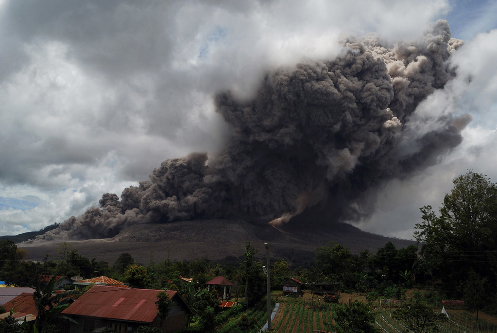 . Dark giant ash clouds rise from the crater of Mount Sinabung volcano during an eruption on October 8, 2014, as seen from Karo district located on Indonesia\'s Sumatra island, following an earlier eruption on October 5, 2014.According to authorities hundreds of residents are still housed at evacuation centers as authorities maintains off limit danger zone around Mount Sinabung located in Indonesia\'s Sumatra island following deadly eruption in early February that killed about 17 people.  AFP PHOTO / SUTANTA  ADITYA/AFP/Getty Images