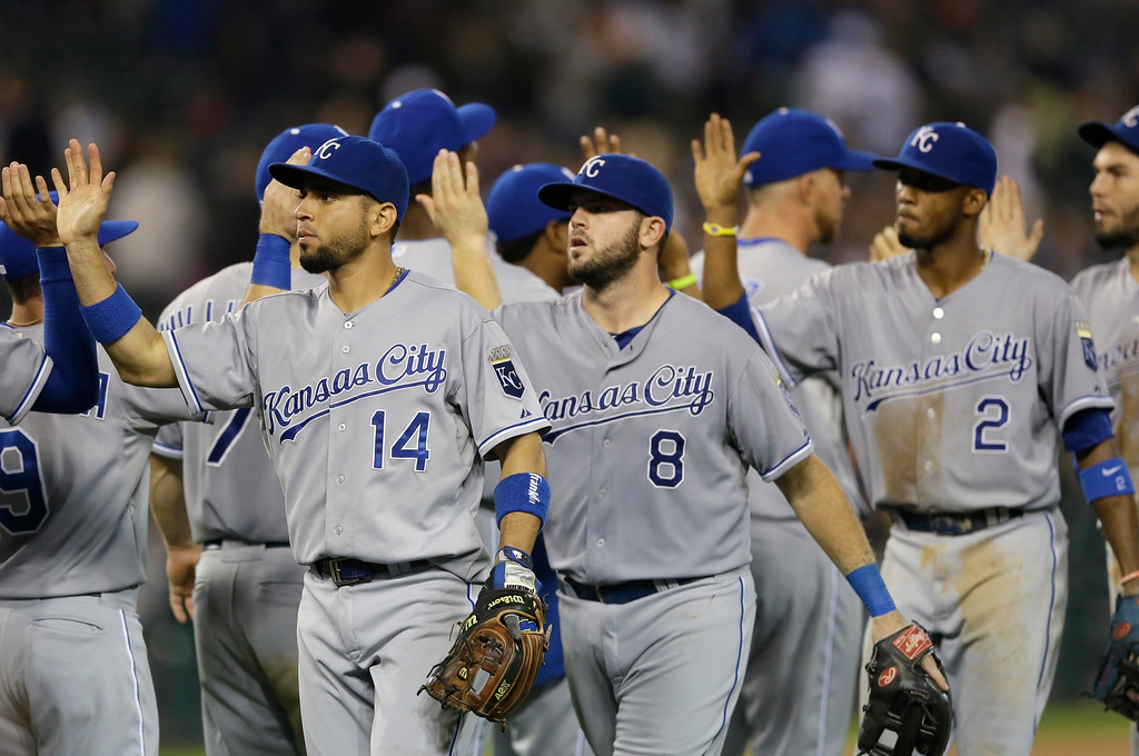 . Kansas City Royals second baseman Omar Infante (14), third baseman Mike Moustakas (8) and shortstop Alcides Escobar (2) celebrate their 3-0 win over the Detroit Tigers in a baseball game in Detroit, Wednesday, Sept. 10, 2014. (AP Photo/Carlos Osorio)