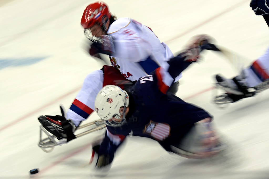 . Russia\'s Vasilii Varnakov (top) vies with US Joshua Pauls during a Sledge Hockey match between Russia and USA at XI Paralympic Olympic games in the Shayba stadium near Sochi on March 11, 2014.  KUDRYAVTSEV/AFP/Getty Images