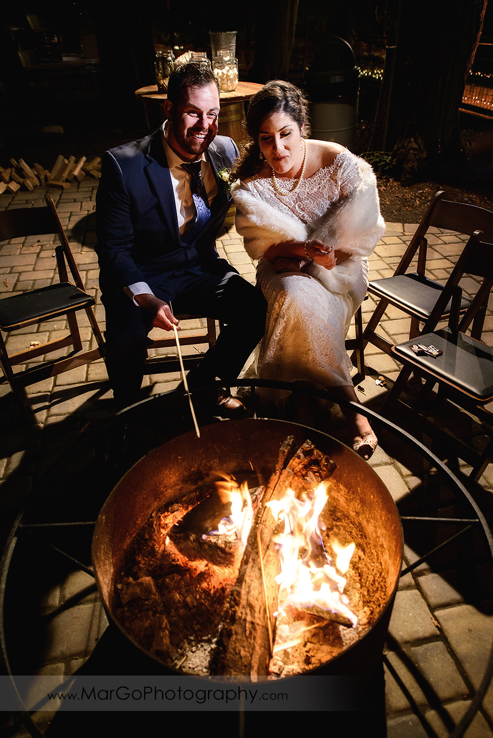 bride and groom sittinf next to fire pit during at Saratoga Springs Cathedral Grove