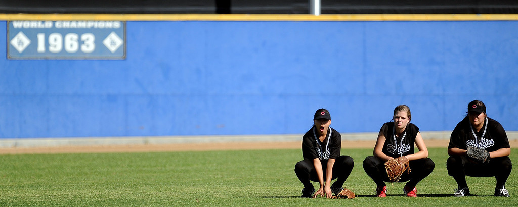 . Corona Centennial outfielders take a break in between the first inning of Charter Oak softball Tournament semifinal softball game against Bonita at the Big League Field of Dreams Park on Friday, March 15, 2013 in West Covina, Calif. Corona Centennial won 5-1.  (Keith Birmingham Pasadena Star-News)