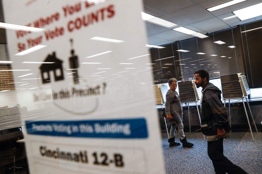 . Polling workers mill about an empty voting location at the University of Cincinnati, Tuesday, Nov. 7, 2017, in Cincinnati. Ohio voters will decide ballot issues on Tuesday that would place limits on drug prices and expand victims\' rights in criminal proceedings, along with several mayoral races. (AP Photo/John Minchillo)